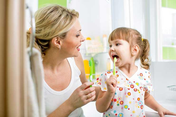 Kind mit Mama beim Zähne putzen